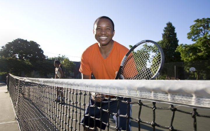 Man playing tennis. He holds his racket and stands near the net as he smiles. Horizontally framed photo.