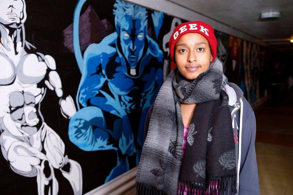 young woman standing next to an art graffiti wall