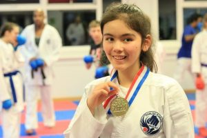 young girl with karate medal compressed 300x200 - Karate at YMCA Hawker in Kingston