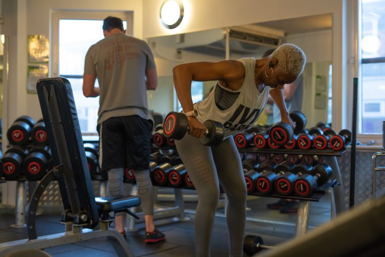Women training lifting weights in gym