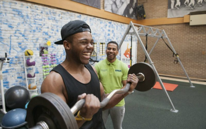 Young man lifting weights in gym with personal trainer