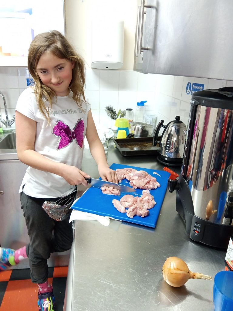 Hampton Youth Project. Young girl cooking cutting chicken
