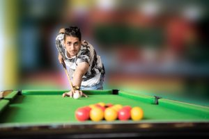 Young man playing a game of pool