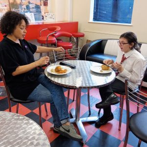 Young woman and a youth worker enjoying a meal