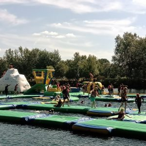 young people playing on inflatables in the water