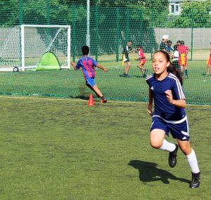 Young girl running on a sports field