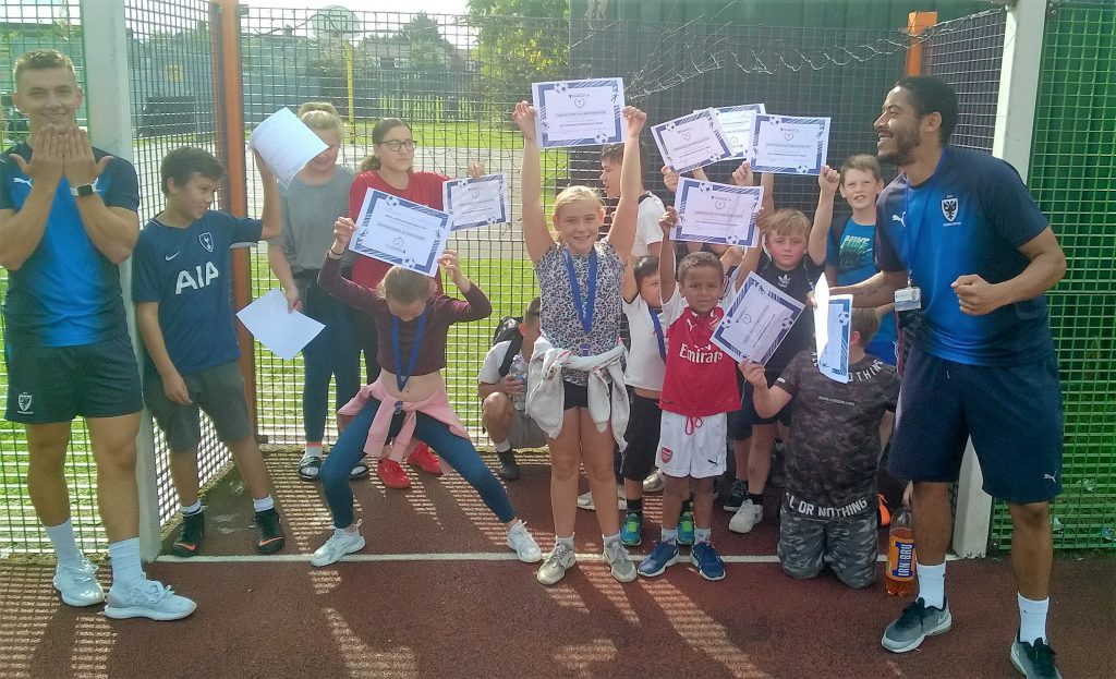 Group of young people receiving an award after completing a football course.