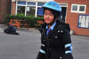 Girl playing with helmet and pads