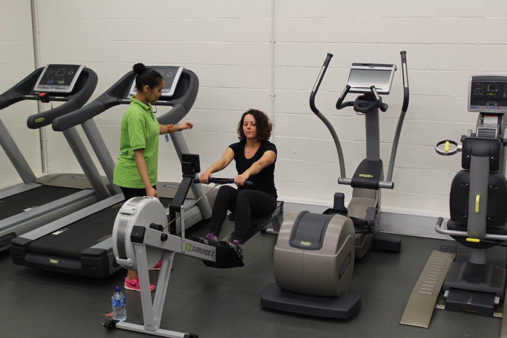 Women in gym on exercise machine with personal trainer