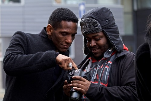 Two men checking a camera for photographs