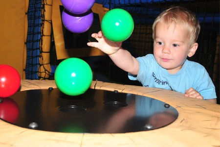 Kid throwing balls on to table