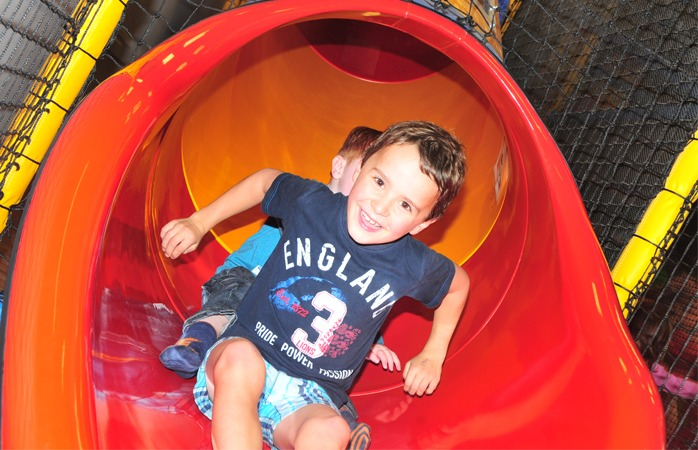 Children on slide in soft play pod