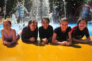Group shot of kids by a play water fountain